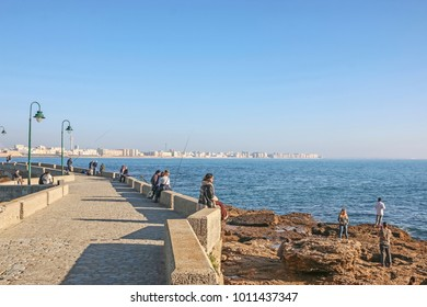 CADIZ, SPAIN - AUGUST 31, 2017: Tourists strolling along Paceo Fernando Quinones leading to Castle of San Sebastian at Caleta Beach, ancient defense fortress and culture exposition center at present