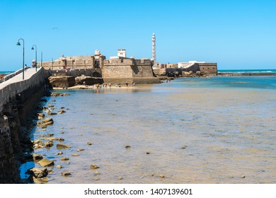 Cadiz,Spain-august 9, 2017:people on the beach near the San Sebastian castlen and the iron lighthouse in Cadiz  during a sunny day
