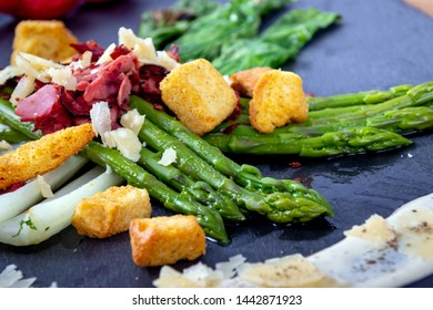 caesar asparagus with sliced parmesan cheese, smoked meat and crouton gourmet cuisine dish