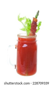 Caesar made with vodka and clamato juice, served in a spicy rimmed mason jar and garnished with fresh celery and asparagus wrapped in crispy bacon. Shot on white background.