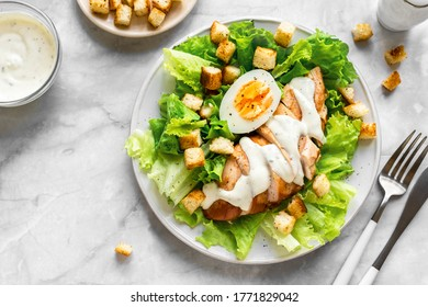 Caesar salad with chicken breast on marble background, top view, close up. Fresh chicken salad for healthy lunch.