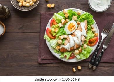 Caesar salad with chicken breast on dark wooden background, top view, copy space. Fresh chicken salad for healthy lunch.