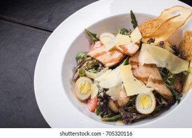 Caesar salad with chicken and quail eggs in white plate