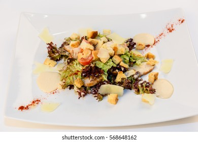 Caesar salad with chicken, vegetables and greens on a white background