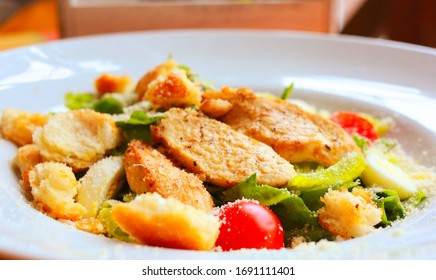 Caesar salad with croutons, quail eggs, cherry tomatoes and grilled chicken in a white plate on a table in a restaurant. Close-up