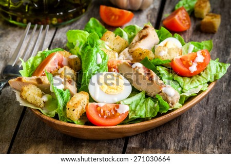 Caesar salad with croutons, quail eggs, cherry tomatoes and grilled chicken in wooden plate on dark rustic table