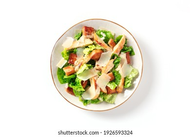 Caesar salad with grilled chicken meat, romaine and Parmesan, shot from the top on a white background