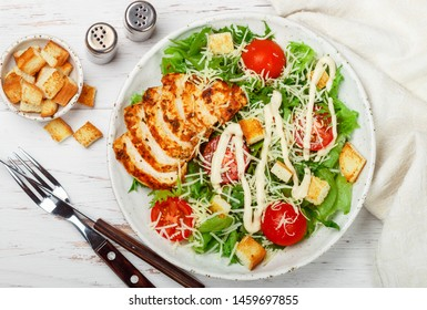 Caesar Salad. Healthy Grilled Chicken  with iceberg or lettuce, Cheese Parmesan, cherry tomatoes, bread Croutons and  gourmet  dressing. Selective focus, top view