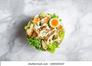 Caesar Salad on marble table, top view, copy space. Homemade chicken caesar salad with grilled croutons.