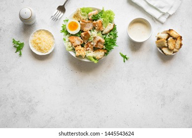 Caesar Salad on white table, top view, copy space. Homemade chicken caesar salad with grilled croutons.