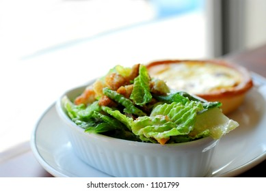 Caesar salad and quiche on white plate