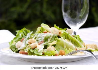 Caesar Salad, served in a garden setting.  Healthy al fresco dining.