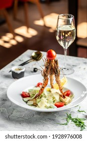 Caesar Salad with Shrimp. Caesar salad with king prawns in a white plate. Restaurant menu, dieting, cookbook recipe.