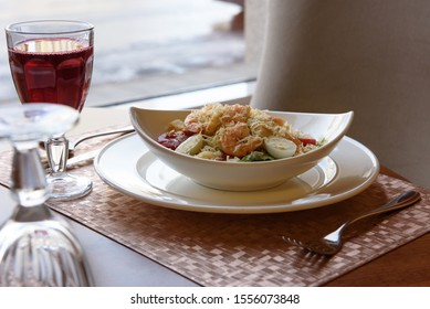 Caesar salad with shrimp on a table with a drink