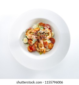 Caesar Salad with Tiger Shrimps, Croutons, Tomatoes and Greens Isolated on White. King Prawns Salat with Romaine Lettuce Dressed with Lemon Juice, Olive Oil and Grated Parmesan Cheese Top View