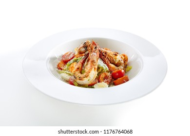 Caesar Salad with Tiger Shrimps, Croutons, Tomatoes and Greens Isolated on White Background. King Prawns Salat with Romaine Lettuce Dressed with Lemon Juice, Olive Oil and Grated Parmesan Cheese