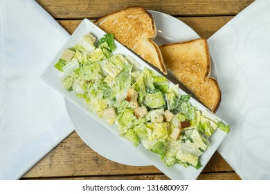 Caesar Salad with toast bread on wooden table