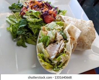 Caesar Salad Wrap - Mahi Mahi Fish Wrapped in a Flour Tortilla with Baby Romaine, House-made Ceasar Dressing and Parmesan Crisps with salad.
