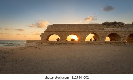 Caesarea, Israel - 25 June, 2018: Visitors relaxing on remnants of the ancient Roman Aqueduct at sunset.