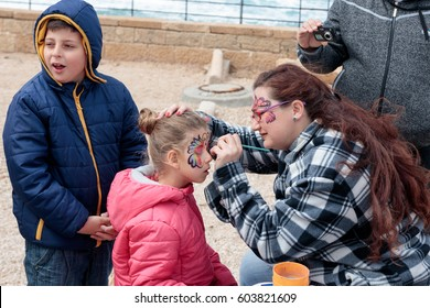 Caesarea, Israel, March 11, 2017 : Participant of the Purim festival applies a butterfly drawing on the girl's face in Caesarea, Israel