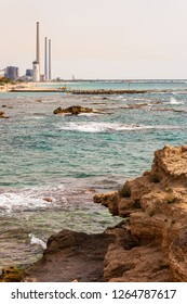 Caesarea, Israel - May 22, 2012: Rocks on the beach, rocky Mediterranean sea coast waters and Orot Rabin, a coal-fired power station
