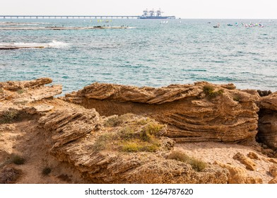 Caesarea, Israel - May 22, 2012: Rocks on the beach, fishing fishermen on flat stone, many surfers in the Mediterranean sea waters and Orot Rabin, a coal-fired power station