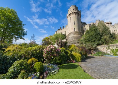 Caesar's Tower part of the dramatic Warwick Castle fortress, with trees and flowers of Mill Garden below, beautiful blue spring sky, April 2017, Warwick, Warwickshire, United Kingdom, UK