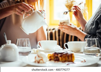 Cafe or bar table with desserts and tea. Two people talking on background.