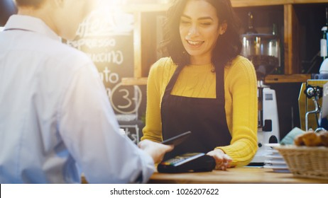 In the Cafe Beautiful Hispanic Woman Makes Takeaway Coffee For a Customer Who Pays by Contactless Mobile Phone to Credit Card System.