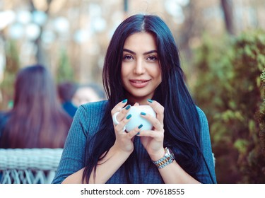 Cafe city lifestyle. Indian woman sitting at the balcony terrace of a fancy in coffee shop restaurant holding cup of hot beverage tea. Cool young modern female model. Positive face expression emotion