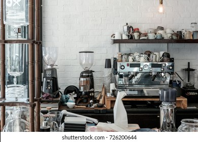 Cafe / coffee shop bar and counter with coffee equipment: espresso coffee machine, coffee grinder, cups for drink preparation by barista