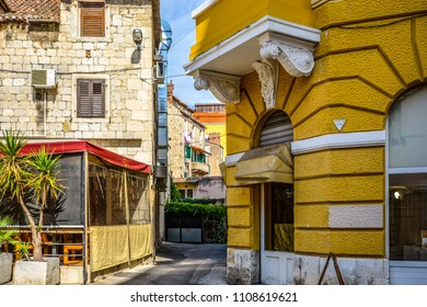 A cafe and colorful business on a typical streetcorner in the old town section of Split Croatia with the residential area behind.