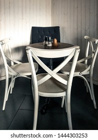 Cafe interior with white chairs and vintage wooden background wall