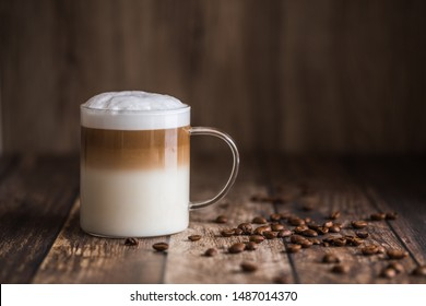 Cafe latte macchiato layered coffee in a see through glass coffee cup. The cup is on a wooden background with coffee beans on the table next to the cup.