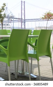Cafe in Lisbon. Green plastic chair and metalic table.