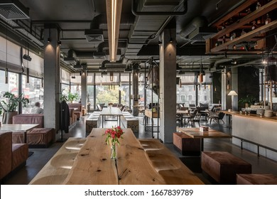 Cafe in a loft style with big panoramic windows and concrete columns. There are wooden tables, benches, poufs, sofas, chairs, shelves with bottles, glass coffee bean dispensers, hangers, equipment.