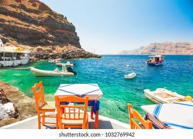 Cafe on the sea coast in the port of Santorini island, Greece.
