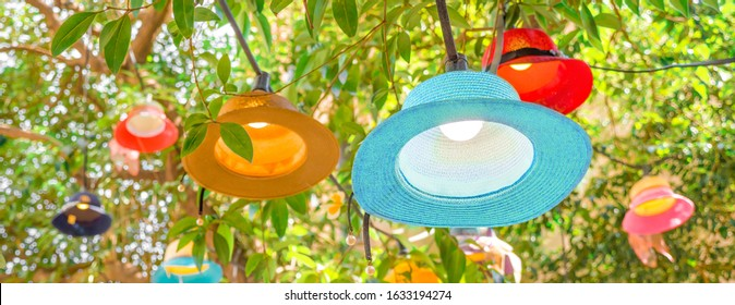 Cafe outside light decor closeup. Summer concept. Vacation, travel conceptual. New life for old hats, panamas. Decoration with pamana and hats. Original multi-colored lampshades hanging on tree Banner