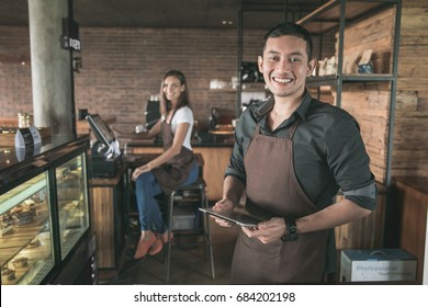 cafe owner at his coffee shop using tablet pc. his partner sitting in a background