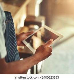 Cafe owner holding digital tablet in hands