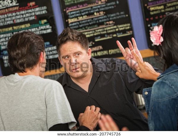 Cafe owner talking with rude customers in line