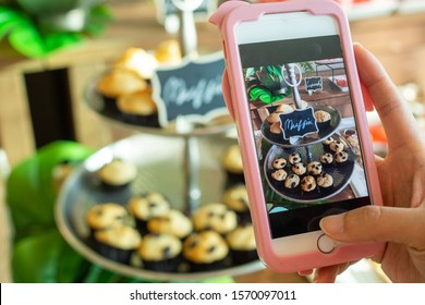 The cafe owner uses a smartphone to take pictures of newly finished cupcakes to promote on online media and websites. Selling products online