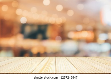 Cafe Restaurant interior with customer and wood table blur abstract background with bokeh light for montage product display