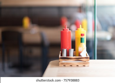 A cafe or restaurant tabletop setup with ketchup and mustared bottles and a salt and pepper shakers.