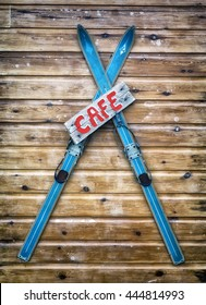Cafe Sign, antique wooden skis being using as part of a cafe sign on the side of a log cabin.