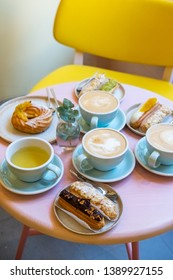 Cafe table with cups of coffee, eclairs and cake