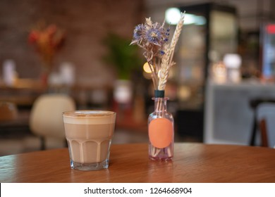 Cafe table decorated with dry grass and flowers in small glass bottle with glass of flat-white coffee standing near with blurred interier on background