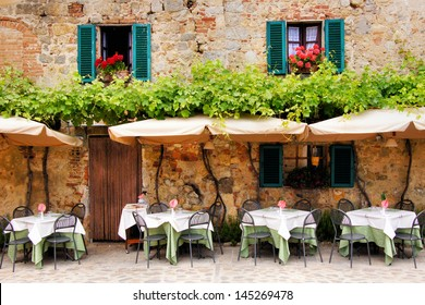Cafe tables and chairs outside a quaint stone building in Tuscany, Italy