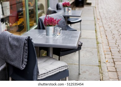 Cafe tables stand on the street.