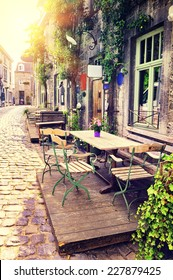 Cafe terrace in small European city at sunny summer day
